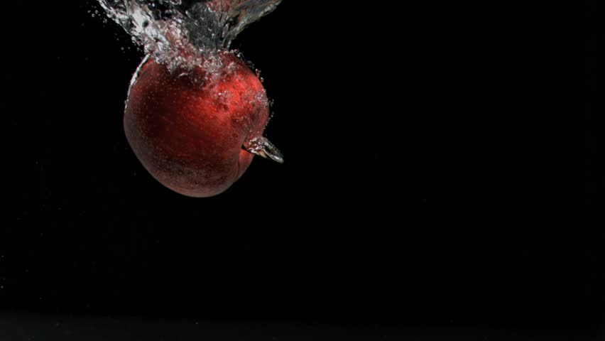 Red apple in super slow motion falling in the water against a black background