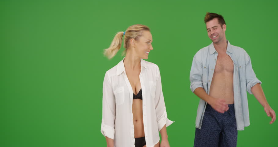 Attractive Caucasian millennial couple standing at the beach smiling at camera on green screen. On green screen to be keyed or composited.