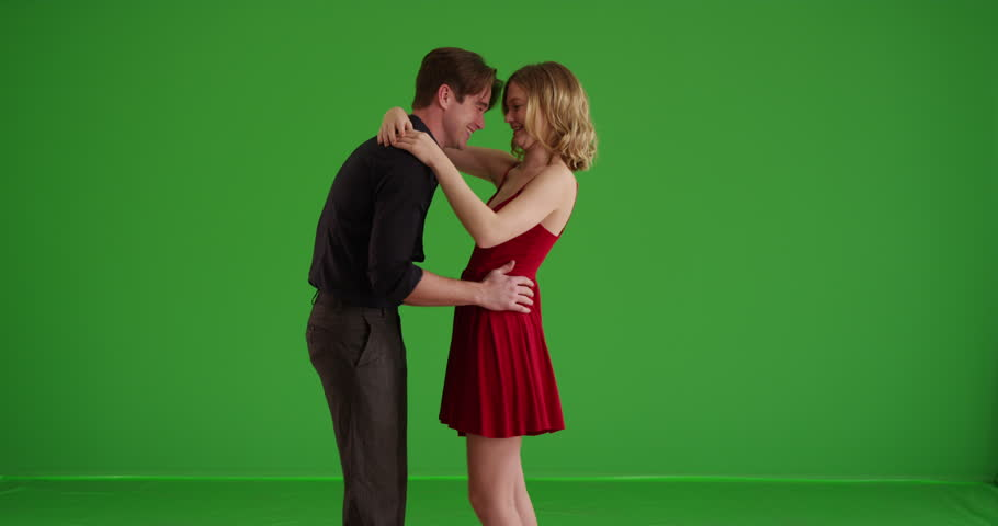 Young white couple flirting, dancing and spinning on green screen. On green screen to be keyed or composited.