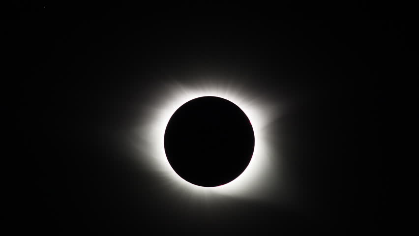 The Sun's corona is visible during the total eclipse phase of the Great American Eclipse on August 21, 2017.  Pinkish solar flares are also visible near the Sun's surface.
