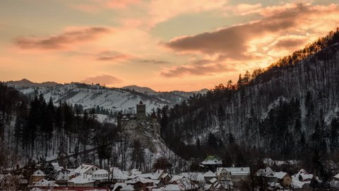Bran castle at sunset in winter. Panoramic view with dramatic sky at sunset over Bran village, Romania.  4k timelapse.