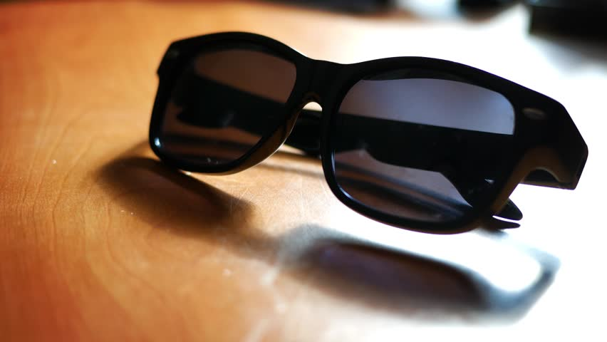 Man picks up sunglasses off office table in summer