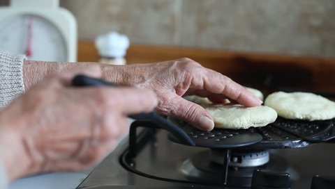 Senior woman hands turning the arepa over on the grill