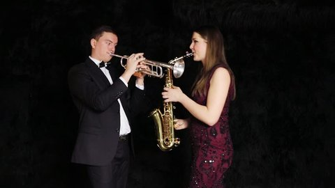Man and a woman play on wind instruments and turn towards the camera