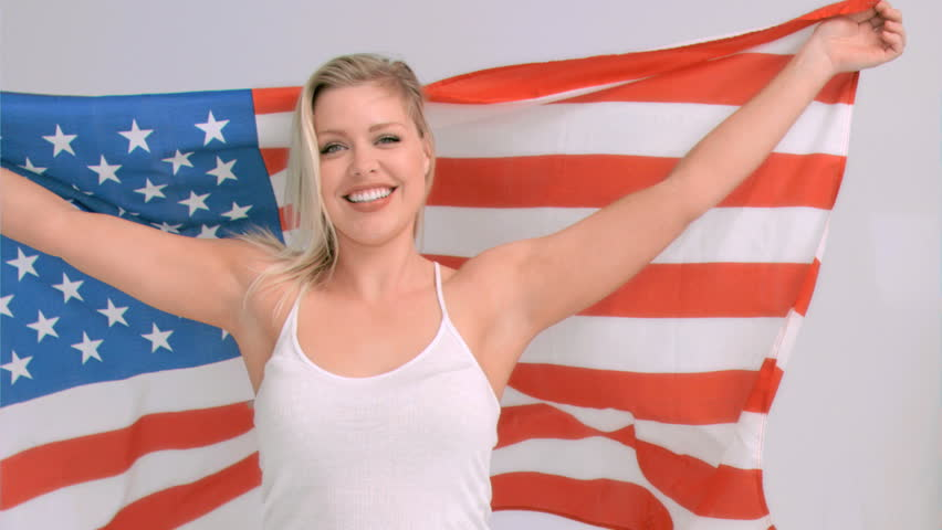 Blonde woman in slow motion raising the Old Glory flag against a grey background