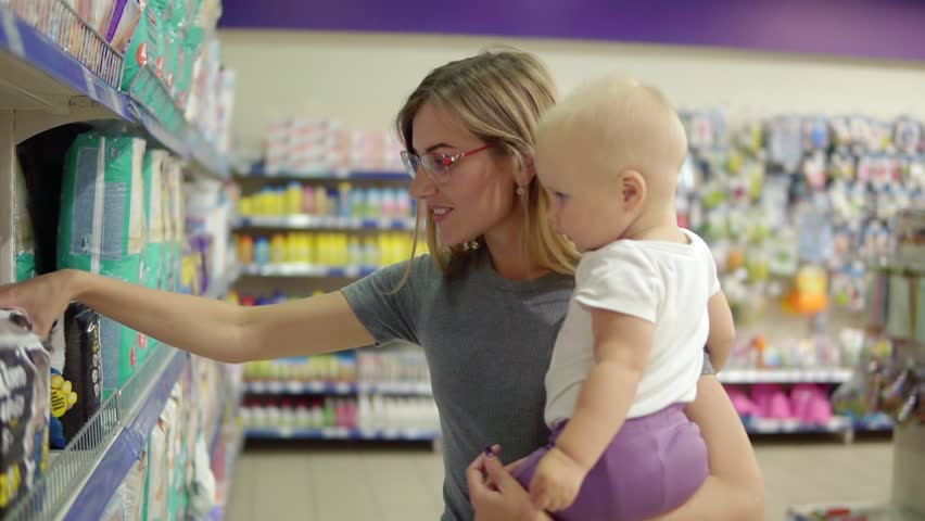 Young attractive mother in glasses holding her child in her arms while choosing diapers on the shelves in the supermarket. Thoughtful mom carefully choosing best products for her child