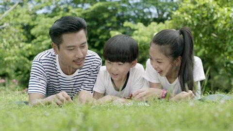 asian father & his children lie on grassland reading story book