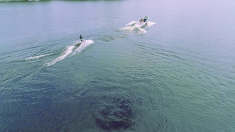 Flying over wakeboarding on river 4k aerial video. Wakeboarder surfing behind boat trails and doing tricks: somersault flip jump