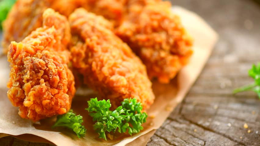 Crispy fried chicken wings and legs on a wooden table rotation 360 degrees. Breaded Crispy fried chicken tasty dinner. 4K UHD video footage. Ultra high definition 3840X2160