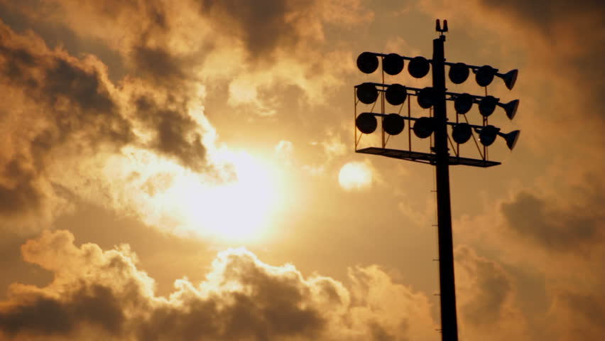Sun setting behind a cloudscape and a silhouetted stadium light, part 2 | Shutterstock HD Video #3020230