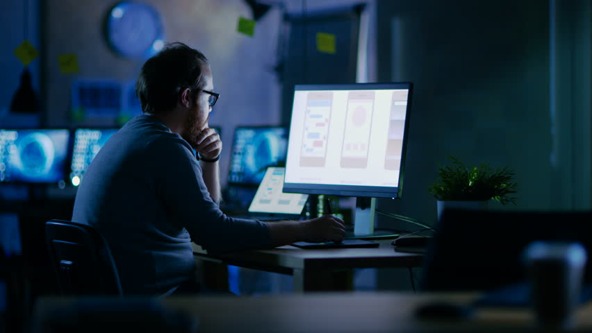 Male Mobile Application Developer Works with Graphics on His Personal Computer with Two Monitors. He Works Late at Night, in an Empty Office. Shot on RED EPIC-W 8K Helium Cinema Camera. | Shutterstock HD Video #30235240