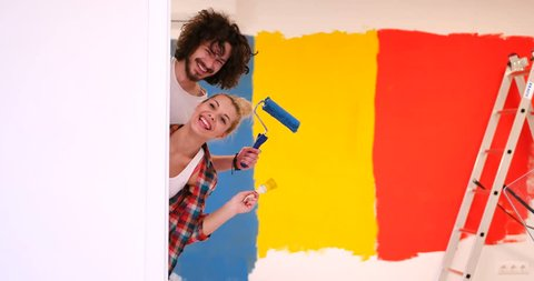 Funny couple just moved into their new appartment and painted wall in crazy colors . Peek a boo behind the wall.