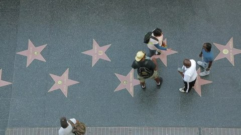Los Angeles, California - April 2017: Walk of Fame on Hollywood boulevard top view. People walking on famous Walk of Fame at Hollywood Blvd. Black sellers of souvenirs on the Walk of Fame in Hollywood