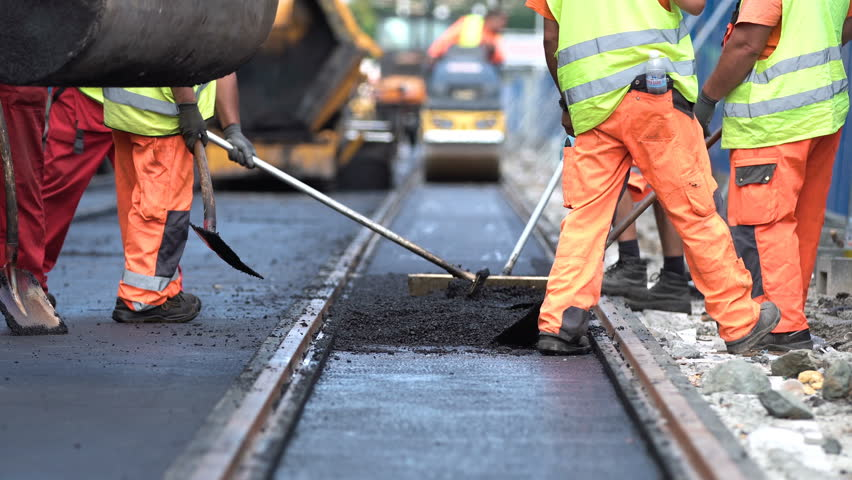Team of workers put the hot asphalt on a street along tram car's railroad lines. Small steamroller. Road construction workers with shovels in protective uniforms. Working in the hot day. | Shutterstock HD Video #30297550