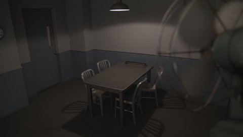 POLICE INTERROGATION ROOM.  Slow, high angle, dolly move from behind an oscillating fan.