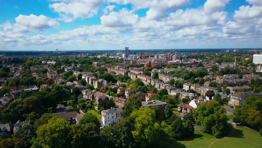Aerial view of a leafy UK suburb on a summers day - camera tracks right