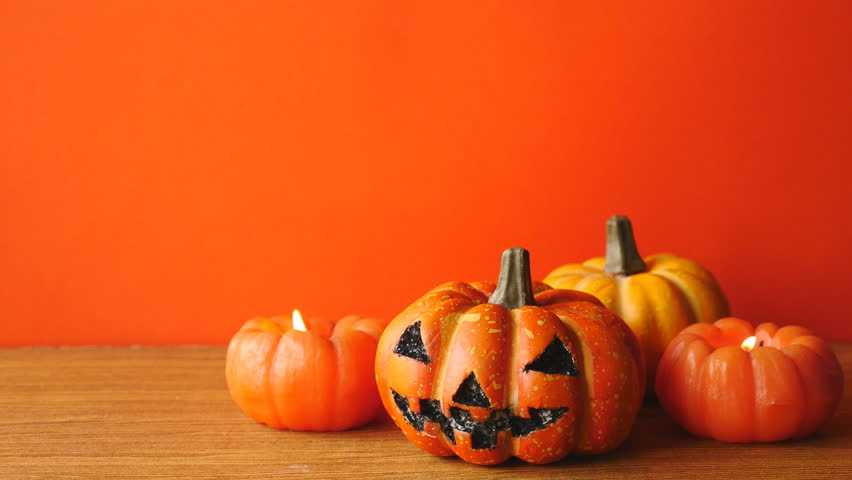 Halloween pumpkins with candlelight on an orange color background. Free space for text