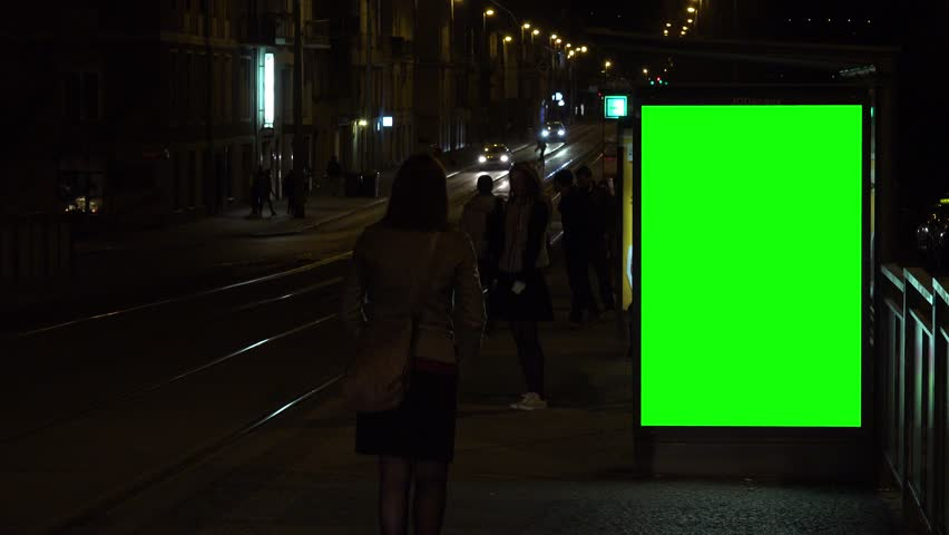 PRAGUE, CZECH REPUBLIC - MARCH 25, 2017: Green screen on the side of a tram stop at night - a tram arrives, people walk out and in