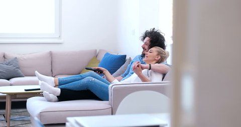 couple relaxing and watching tv in living room