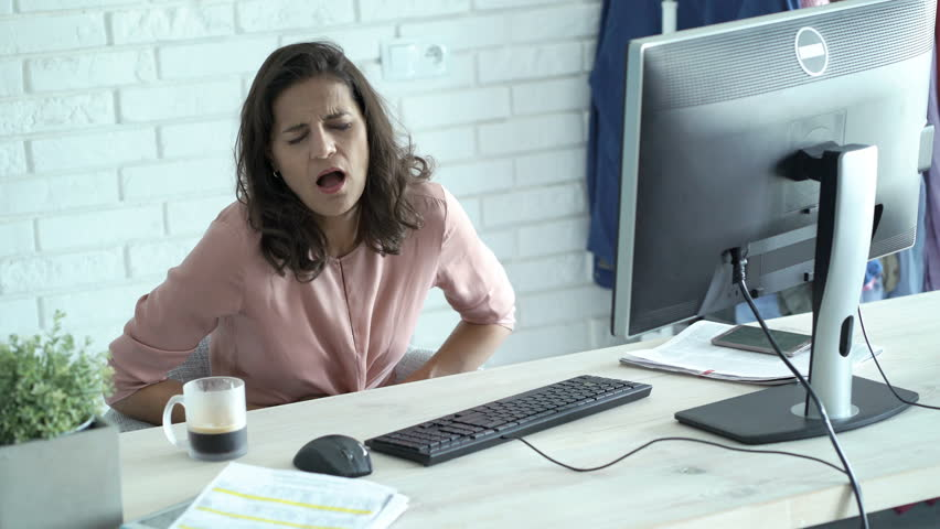 Businesswoman having stomach pain while working on PC computer in office