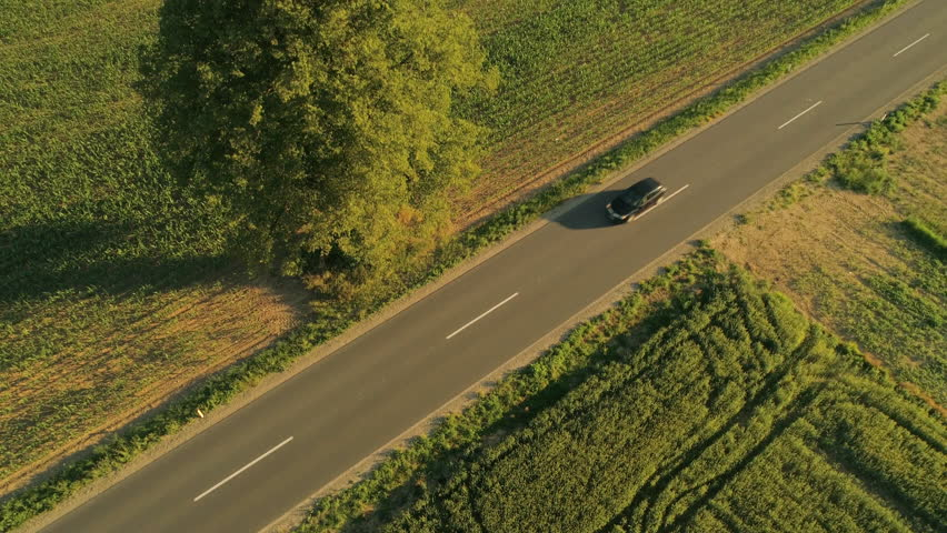 AERIAL, TOP-DOWN: Flying above interstate highway running through picturesque nature in agricultural countryside. People on road trip driving in cars and SUV vehicles through sunny rural landscape