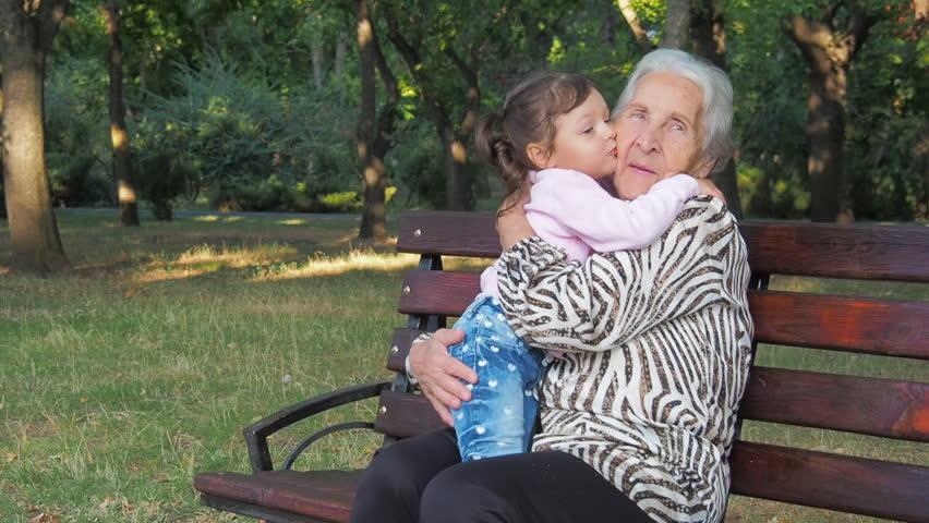 Little girl hugging grandmother. Granddaughter kisses his grandmother.