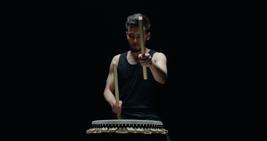 performance of Taiko , Asian male drummer in black clothes, beats a rhythm on a Japanese drum, Steadicam shot, black background