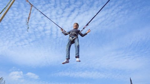 Young boy jumping on bungee trampoline against blue sky, slow motion