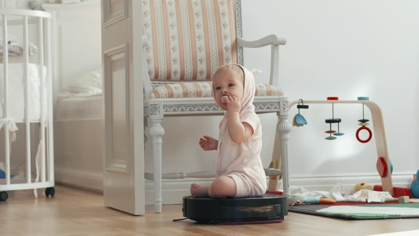 Little girl baby with toddler pacifier moving on a robot vacuum cleaner