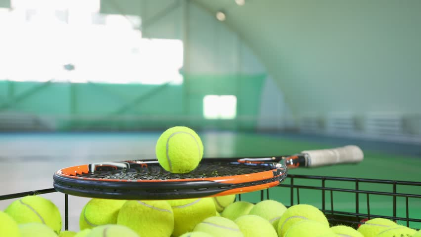 Balls for big tennis in the basket: the tennis player takes the balls and pushes it on the racket. Sports equipment for playing tennis. Hands of a tennis player with a racket. Close-up. | Shutterstock HD Video #30477580