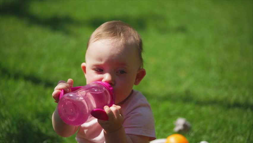 A cute and funny child who holds a plastic bottle in his hands drinks water and looks around, he sits on the grass on a summer day | Shutterstock HD Video #30482830