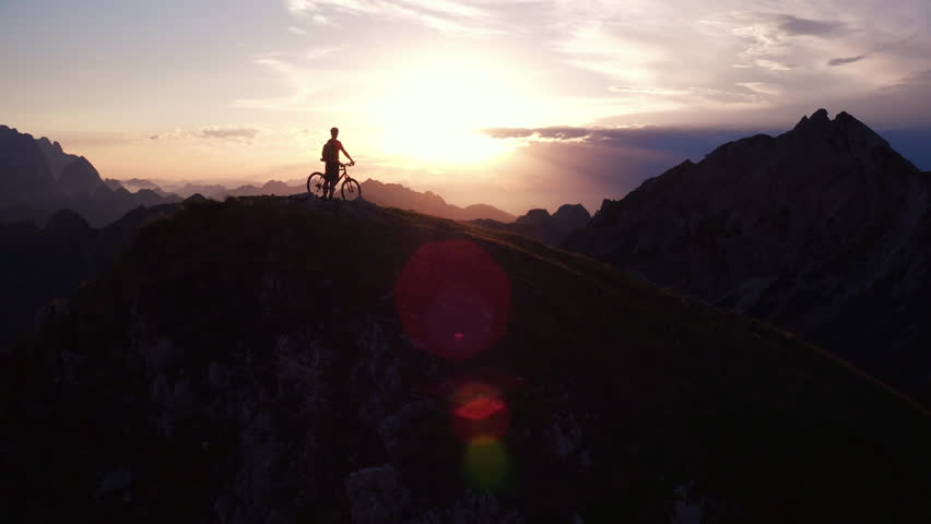 Aerial - Epic shot of a mountain biker standing with his bike on top of the mountain at sunset | Shutterstock HD Video #30511030