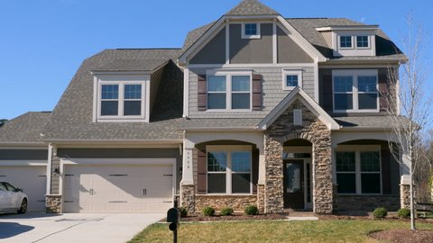 Push in establishing shot of a modern generic suburban middle class home house or mansion with half moon near roof