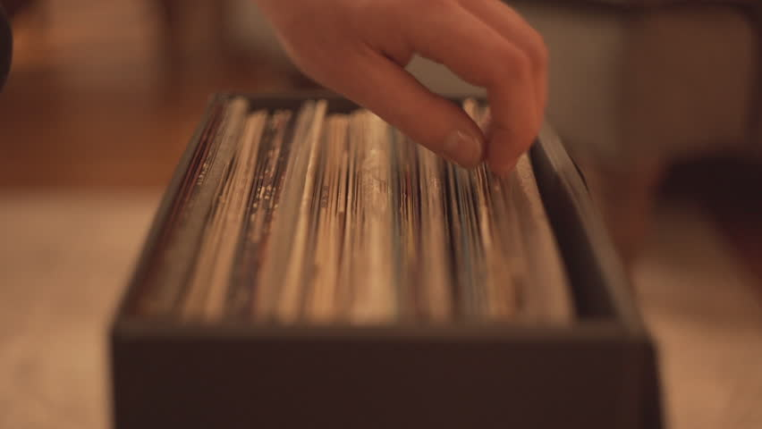 Hand browses vinyl record collection