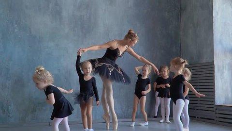 Teachers show how to dance to little ballerinas. Girl dancer in ballet school learns to dance. Young ballerinas jumping in training. School of ballet. Feet closeup