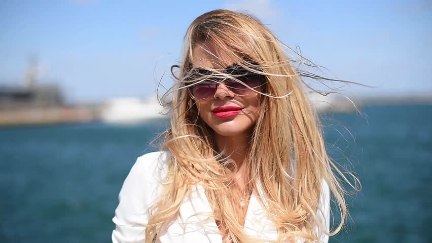 Slow Motion Cute girl with serious facial expression posing on camera putting hair on face against blue sea and sky on warm clear day. Woman of European appearance with blond hair dressed
