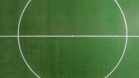 Great overhead crane up shot of green soccer field with midfield and white sidelines. Aerial shot.
