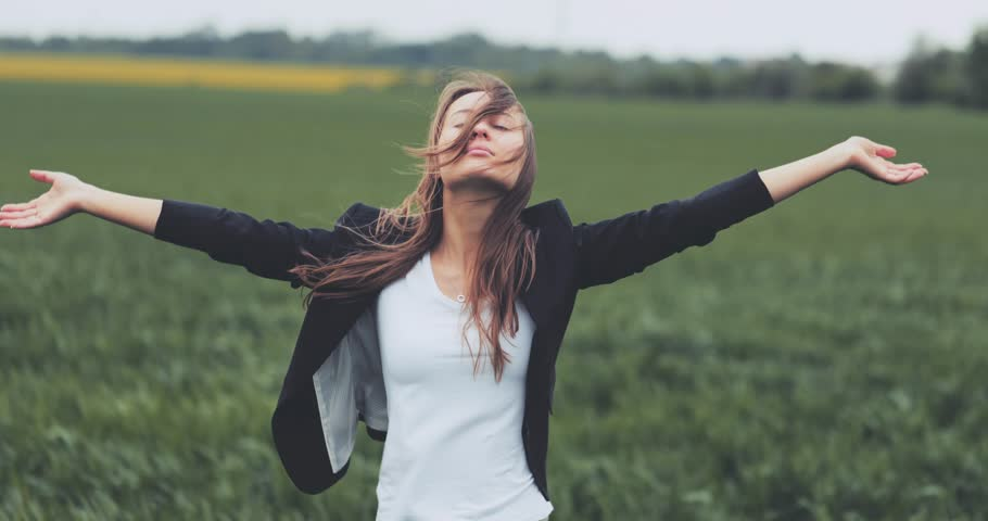 Portrait of Business Woman Standing on the Wind with Hands Up. SLOW MOTION 4K DCi. Businesswoman enjoying the wind, feeling free. Stormy weather, autumn, winter, spring.
