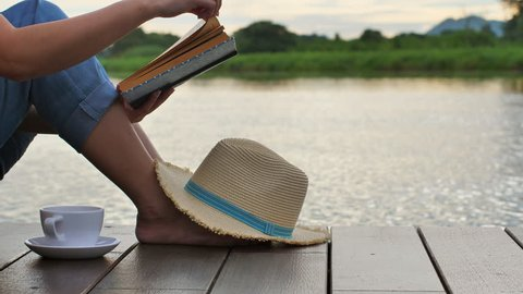 Advertising,Vacation,Time to relax concept - Young Woman reading the book near Lake, Slow Motion. Calm and cozy time in morning and leave space for adding your content.