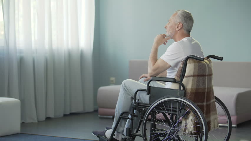 Sad sorrowful lonely old man sitting in wheelchair in his ward nursing house. Depressed handicapped pensioner thinking, healthcare problem, disability. Rehabilitation center client, difficult recovery