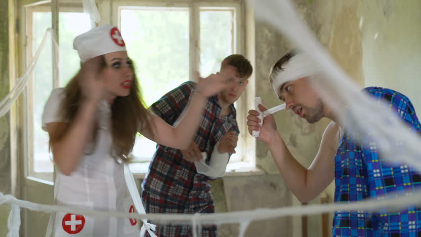 Sexy beautiful young female woman nurse screams and shouts at patients in psychiatric hospital. Psychos catch the doctor in room in mental clinic. Mad crazy people tie up by bandages their doctor