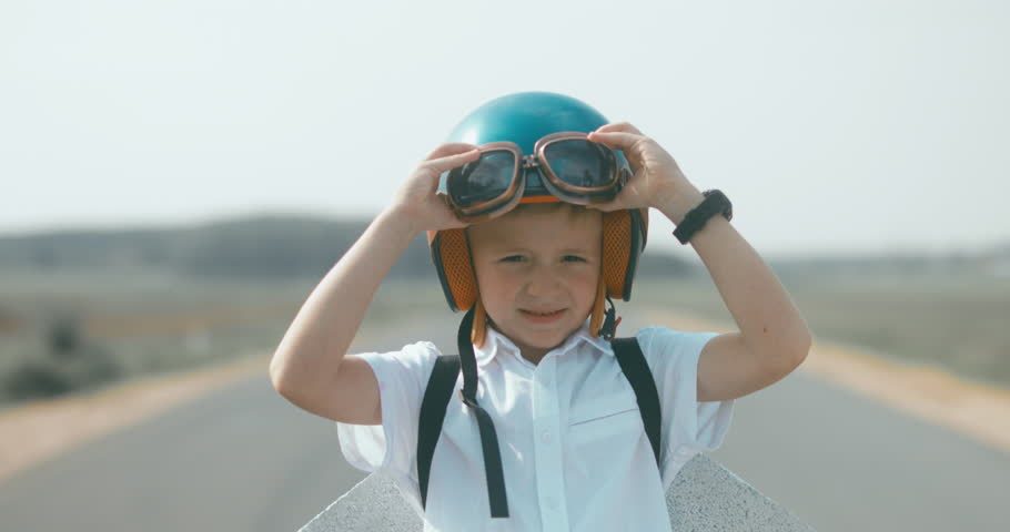 CU Little boy putting on vintage googles and helmet, pretending to be a pilot. 4K UHD RAW edited footage | Shutterstock HD Video #30699520