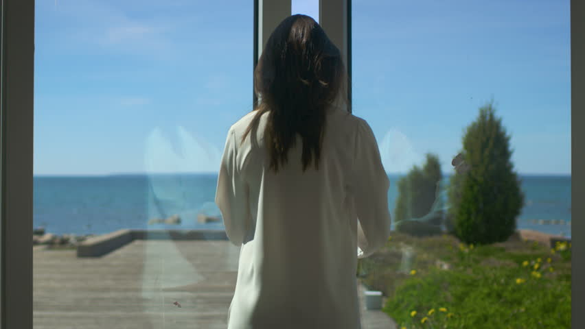 Following Shot of a Beautiful Brunette with Loose Hair Walking on the Sunny Terrace with Seaside View. It's Cloudless Morning and She's Really Happy. Shot on RED EPIC-W 8K Helium Cinema Camera.