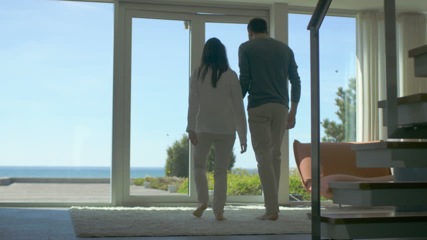 Following Shot of a Beautiful Couple Opening Balcony Doors and Walking onto Sunny Terrace with a Seaside View. Sky is Cloudless and People are Happy. 4K UHD. | Shutterstock HD Video #30700870