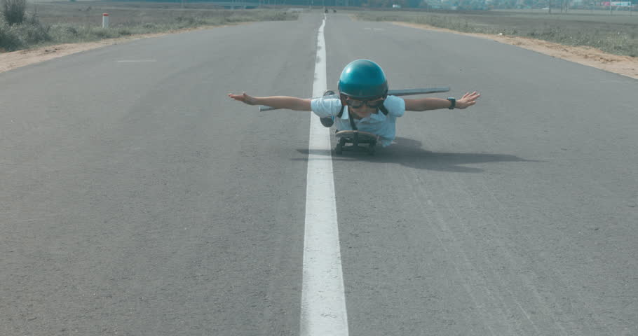 Little boy wearing helmet and styrofoam wings riding skateboard on a rural road, pretending to be a pilot. 4K UHD RAW edited footage | Shutterstock HD Video #30705520