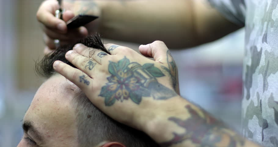 The barber with tattoos on his hands cutting hair using hairbrush and scissors. Close up of hands. Side view. 4K.
