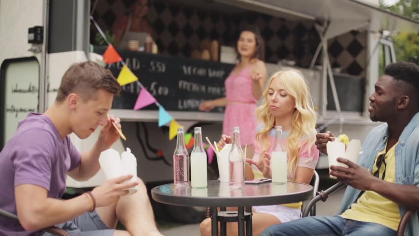 Leisure and people concept - happy friends eating wok and ordering from food truck | Shutterstock HD Video #30711850