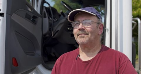 Close up portrait of driver wearing burgundy T-shirt, cap and glasses, looking off into the distance and standing by the cab of his truck. Slow motion with dolly move from left, 4K recorded at 60fps