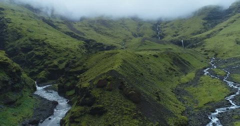 Exotic aerial of foggy green mountains and rivers in Iceland
