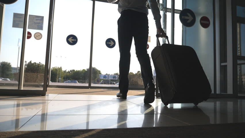 Man going through glass automatic door to the street and roll suitcase on wheels. Businessman walking from the airport with his luggage. Sun flare at background. Trip or travel concept. Slow motion #30718810